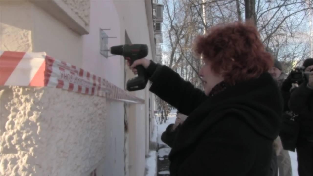 Правнучка Анна Медалье привинчивает табличку (из фильма Олега Дормана).