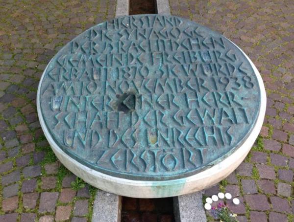 Текст: Здесь стояла синагога Исраэлитской общины Фрайбурга. Построенная в 1870 году, она была 10 ноября 1938 в условиях господства насилия и бесправия разрушена