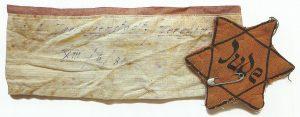 Повязка-браслет Отто Шварца с номером транспорта в концлагерь Терезиенштат. Служила и в качестве удостоверения личности